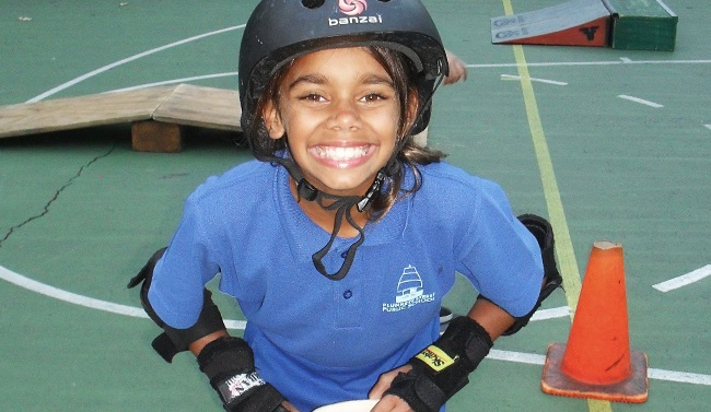 A young student thrilled to be learning how to ride a skateboard at a Skate Now skate camp