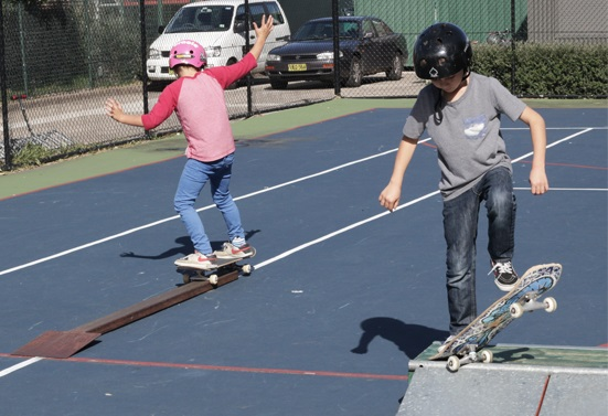 Two students learning to ride a skateboard at a Skate Now skateboarding lesson