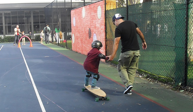 A young student learning to ride a skateboard at a Skate Now skateboarding lessson