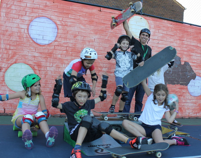 A group of students absolutely stoked after learning to skate at an aftercare skateboarding workshop